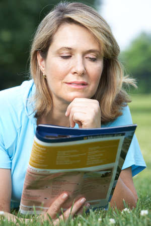 Happy smiling elderly woman reading a magazine