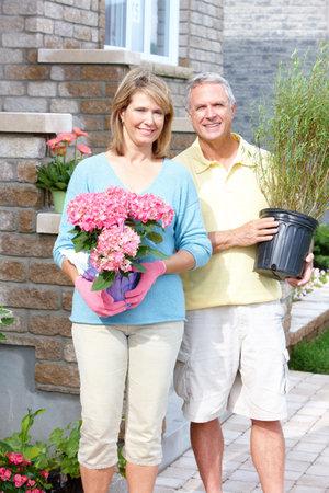 Smiling happy elderly seniors couple gardening near the home  photo