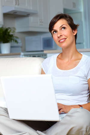 Beautiful smiling woman with laptop  at home  photo