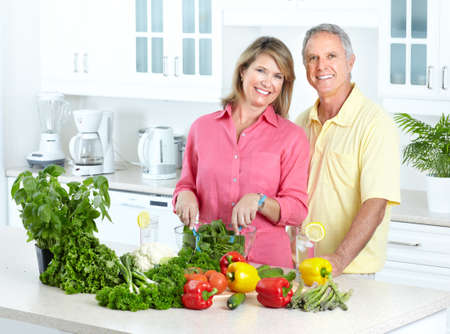 male senior adult: Happy seniors couple cooking at kitchen