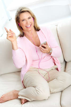Smiling elderly senior woman with a mp3 player at home  photo
