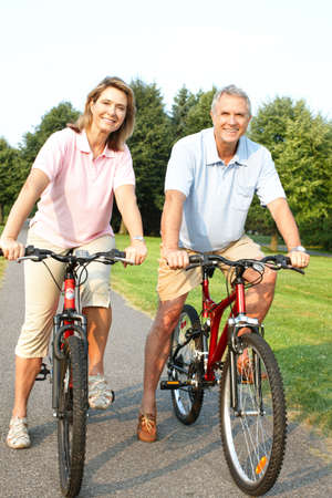 Happy elderly senior couple cycling in park