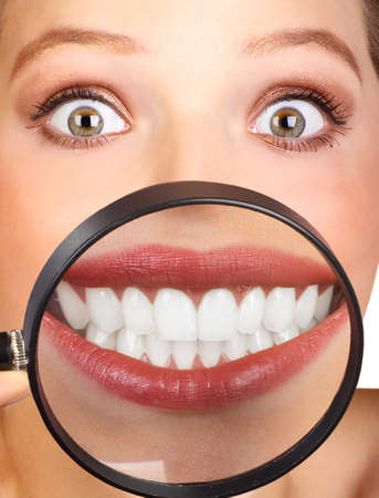dentist smile: Beautiful young woman teeth and magnifying glass