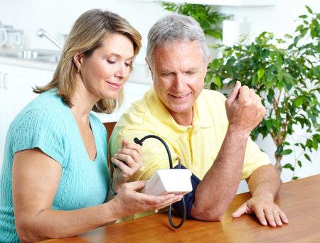 monitoreo: Pareja de las personas de edad en su casa en medir la presi�n arterial. Inicio de supervisi�n