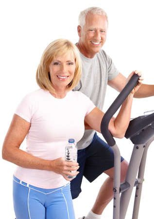 Gym & Fitness. Smiling elderly couple working out. Isolated over white background Stock Photo - 7513406