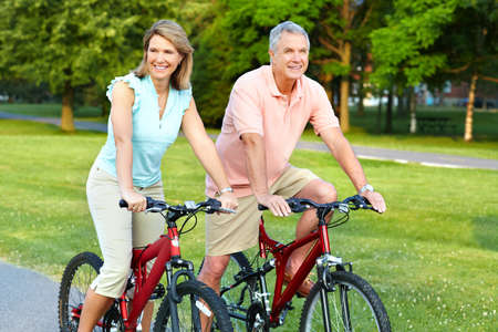 bike riding: Happy elderly senior couple cycling in park