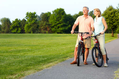 an elderly couple: Happy elderly senior couple cycling in park