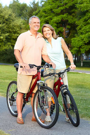 Happy elderly senior couple cycling in park  photo