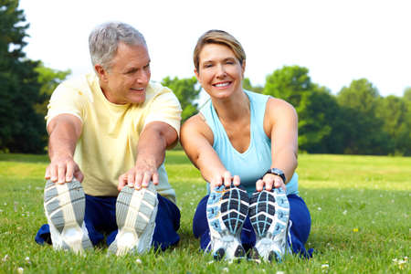 Happy elderly seniors couple working out in park