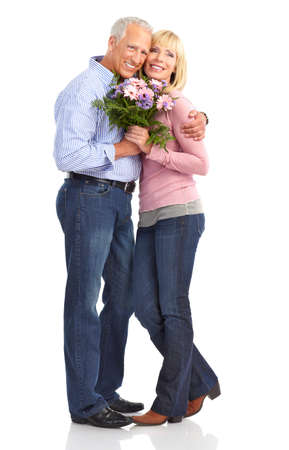 Happy seniors couple in love with flowers.  Isolated over white background photo