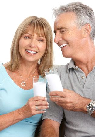 woman drinking milk: Happy elderly couple drinking milk, Over white background  Stock Photo