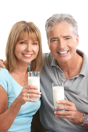 food an drink: Happy elderly couple drinking milk, Over white background  Stock Photo