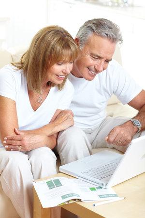 jubilados: Senior par trabajar con el ordenador port�til en casa  Foto de archivo