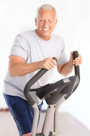 exercitation: Gym & Fitness. Smiling elderly man  working out at home Stock Photo