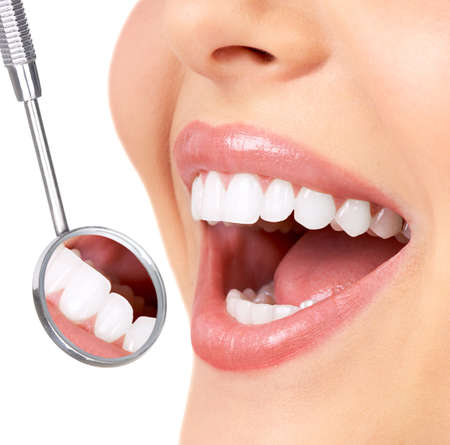 healthy teeth: Healthy woman teeth and a dentist mouth mirror  Stock Photo