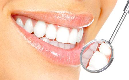 denti: Dientes de mujer saludable y un espejo de boca de dentista  Foto de archivo