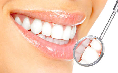smile teeth: Healthy woman teeth and a dentist mouth mirror  Stock Photo