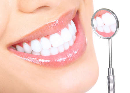 mirror: Healthy woman teeth and a dentist mouth mirror  Stock Photo