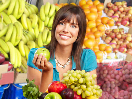 Young smiling woman  with fruits and vegetables.