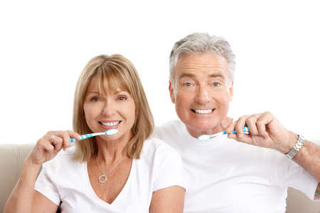 Happy seniors couple with toothbrushes. Healthy teeth. Isolated over white background Stock Photo - 7635047