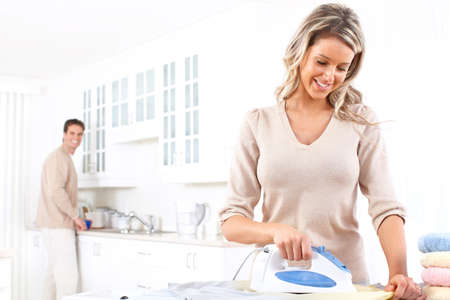 woman ironing: Happy young beautiful woman ironing clothes. Housework   Stock Photo