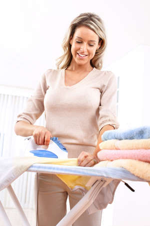 Happy young beautiful woman ironing clothes. Housework   photo