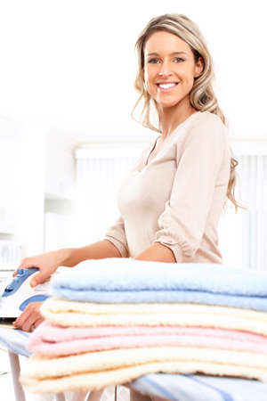 laundry room: Happy young beautiful woman ironing clothes. Housework   Stock Photo