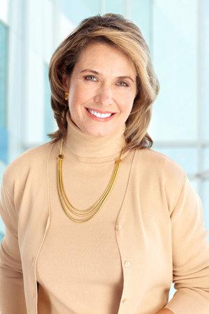 mujeres maduras: Mujer de negocios sonriente. Sobre fondo azul  Foto de archivo