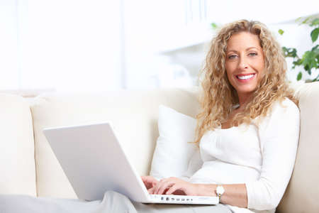 woman on couch: Smiling elderly senior woman with laptop at home  Stock Photo