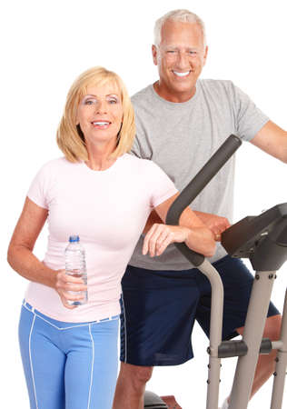 Gym & Fitness. Smiling elderly couple working out. Isolated over white background Stock Photo - 7702702