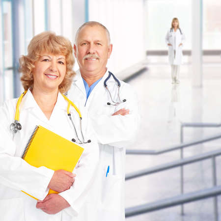 Smiling medical doctors with stethoscopes. Over blue background