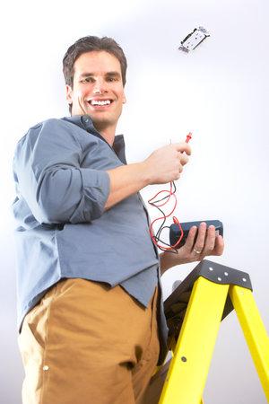 werk: Jonge lachende elektricien doet zijn werk  Stockfoto