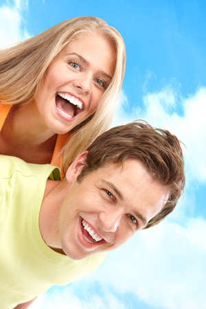 dental smile: Young love couple smiling under blue sky  Stock Photo