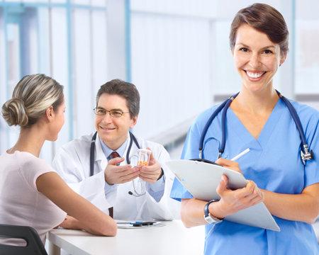 Arts en jonge paar patiënten.   Stockfoto