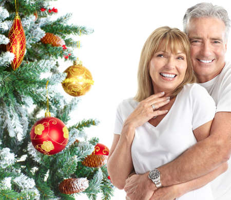 Elderly  happy couple near a Christmas tree. Isolated over white background Stock Photo - 7726405