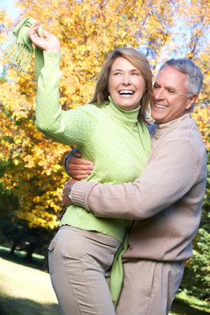 60s adult: Happy elderly seniors couple in park  Stock Photo
