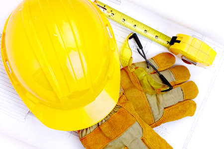 Hard hat, eyeglasses, worker gloves  and ruler over drawing. Renovation tools  photo