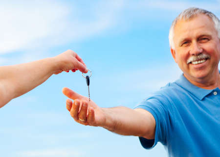 happy smiling man  holding a car key  photo