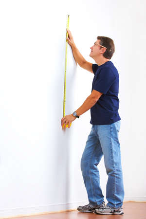 Handsome man with ruler.  Renovation  photo