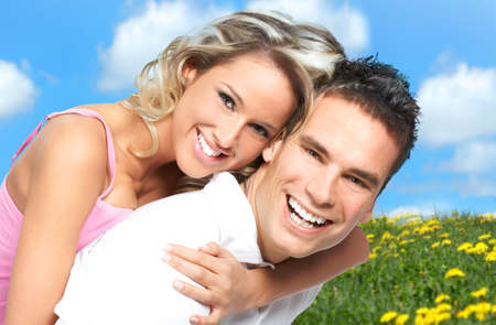 smiling young man: Young love couple smiling under blue sky  Stock Photo