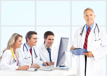 medical doctors: Smiling medical doctors with stethoscopes working with computer.