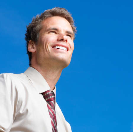 Happy successful  businessman  under blue sky. Portrait  photo