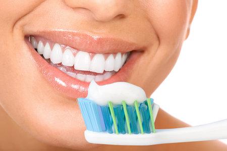 歯ブラシを保持している健康な歯と笑顔の若い女性