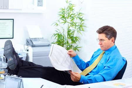 Serious businessman reading newspaper in the office  photo