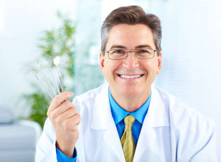 a dentist: Smiling dentist with tools in the office