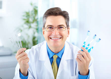 office uniform: Smiling dentist with toothbrushes in the office