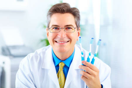 dental medicine: Smiling dentist with toothbrushes in the office