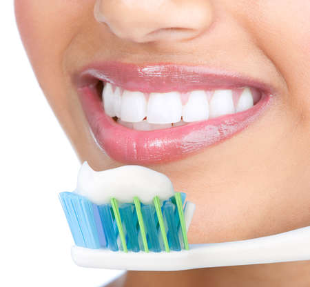 tooth brush: Smiling  young woman with healthy teeth holding a tooth-brush