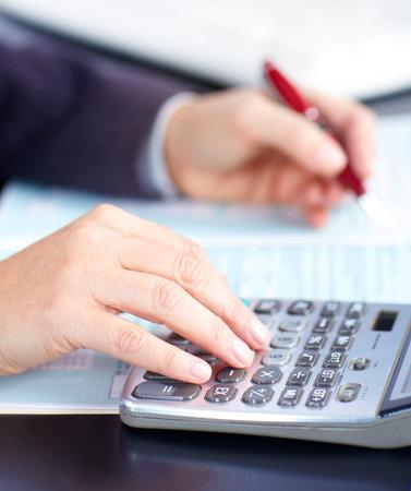 電卓: ビジネスの女性のオフィスでのドキュメントでの作業