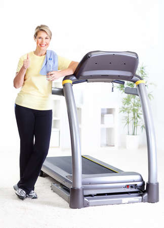 Fitness woman with a bottle of spring water near the treadmill  Zdjęcie Seryjne